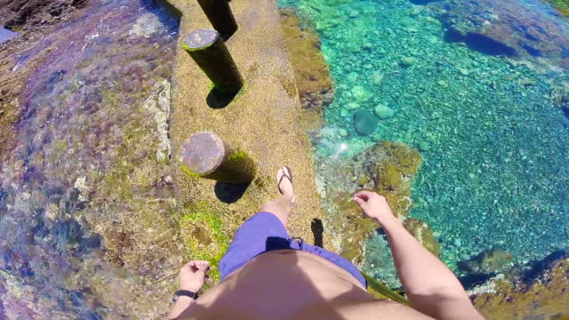 Guy recording from personal perspective walking in the beautiful pool with clear waters in the Tenerife island during travel vacations in the Canary Islands with warm and sunny days.