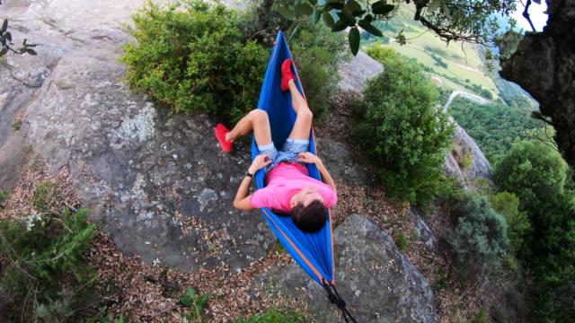 vídeos y material grabado en eventos de stock de guy relaxing in hammock with stunning landscape from viewpoint. - hamaca