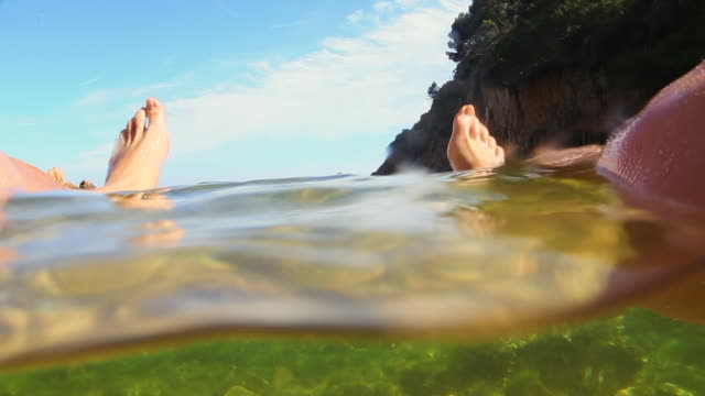 guy relaxing in the beach taking a bath from personal point of view with his legs floating on the water in the costa brava shoreline of catalonia. - 水に浮かぶ点の映像素材/bロール