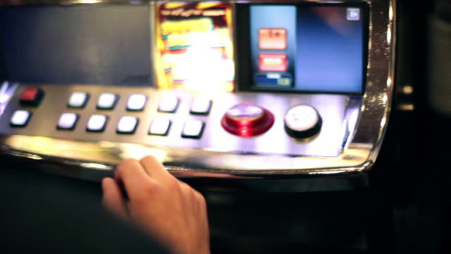 vidéos et rushes de guy selects button and tries his luck at slot machine - hasard