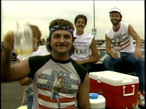 vídeos de stock e filmes b-roll de guy showing off his bruce springsteen shirt while tailgating. - 1985