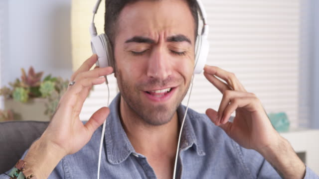 guy singing along to music with headphones