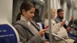 guy  sitting in subway car, browsing in his smartphone