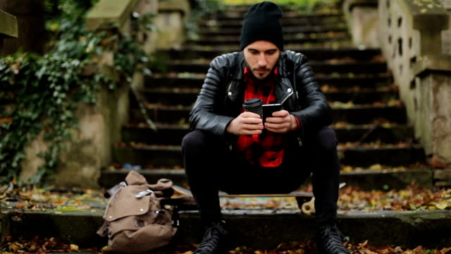 Guy sitting on skateboard and Looking at Smartphone