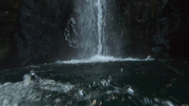 guy swimming from personal perspective under huge waterfall jet of water in the azores islands. - 大西洋諸島点の映像素材/bロール