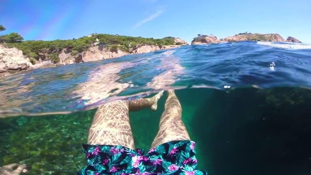 Guy swimming in a paradise turquoise water in Costa Brava.