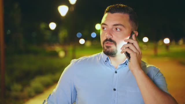 Guy talking on his smart phone outdoors at night close up