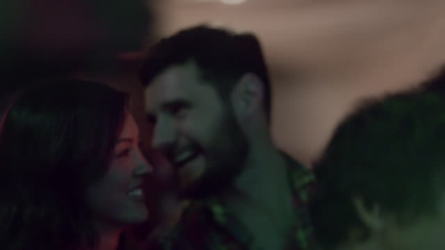 Guy talks in girl's ear as they dance in crowded club at music festival