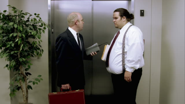 guy walks up to the elevator with old brick cell phone as another guy listens. - brick stock videos & royalty-free footage