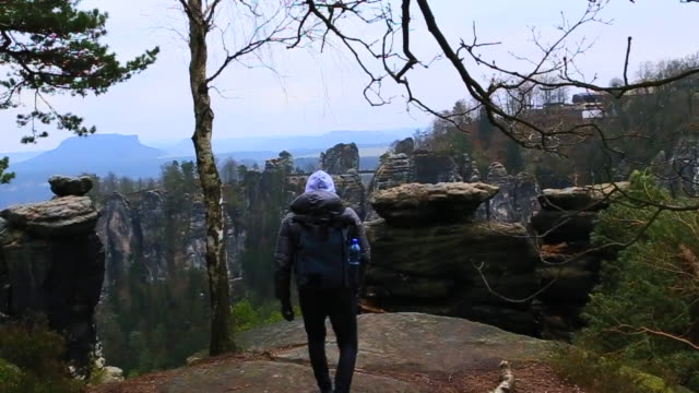 vidéos et rushes de guy with backpack and winter jaquet with cold temperature doing hiking in the beautiful national park in germany with stunning views of the rock formations, contemplating and taking pictures with smartphone of the landscape. - paysage enchanteur