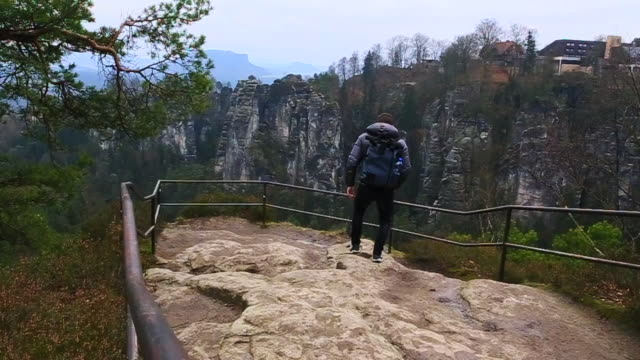 Guy with backpack and winter jaquet with cold temperature doing hiking in the beautiful National Park in Germany with stunning views of the rock formations, contemplating and taking pictures with smartphone of the landscape.