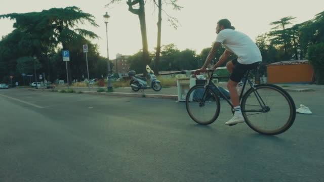guy with beard and tattoo riding a fixie bicycle - gente comune video stock e b–roll