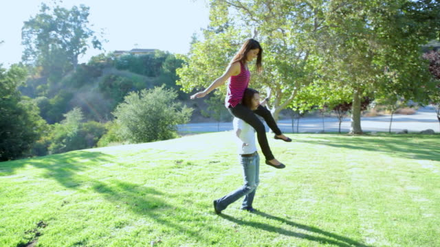 MS TS Guy with girl on his shoulders running around in field / Los Angeles, California, United States