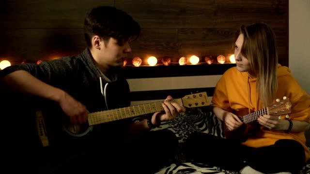 kerl mit mädchen, die mit gitarre und ukulele proben - akkord stock-videos und b-roll-filmmaterial