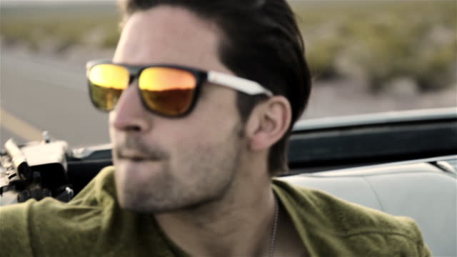 Guy with sunglasses smiles in backseat of classic convertible