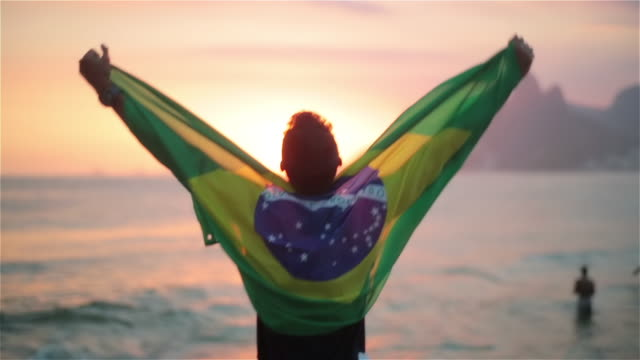 vídeos de stock, filmes e b-roll de guy wrapped in brazilian flag pumps his fists and cheers on ipanema beach at sunset - de braço levantado