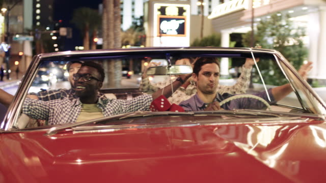 Guys cruise triumphantly through downtown Las Vegas in classic convertible