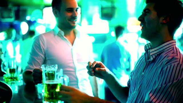vídeos y material grabado en eventos de stock de especulando con una cerveza en el bar. - homosexual