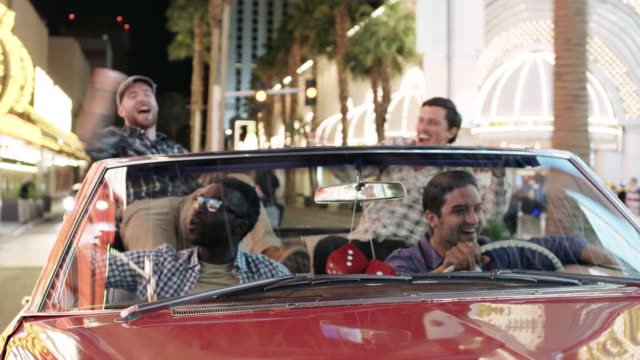 Guys howl and cheer through downtown Las Vegas in classic convertible