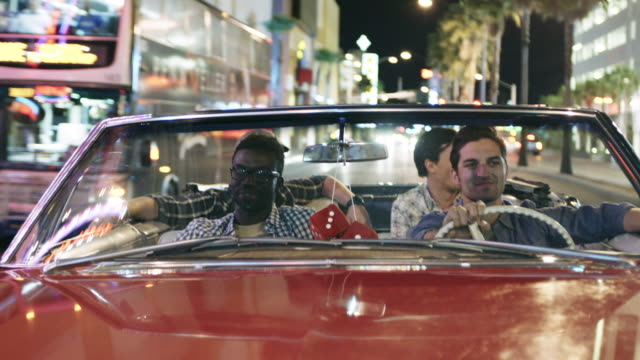 stockvideo's en b-roll-footage met guys in red convertible speed by tour bus in downtown las vegas - dubbeldekker bus