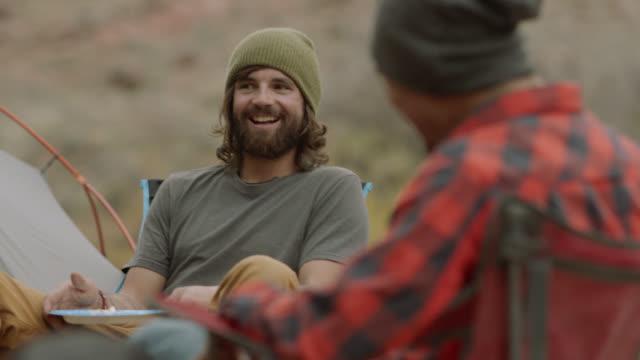 vídeos de stock, filmes e b-roll de guys on camping trip talk and laugh around fire pit. - amizade masculina