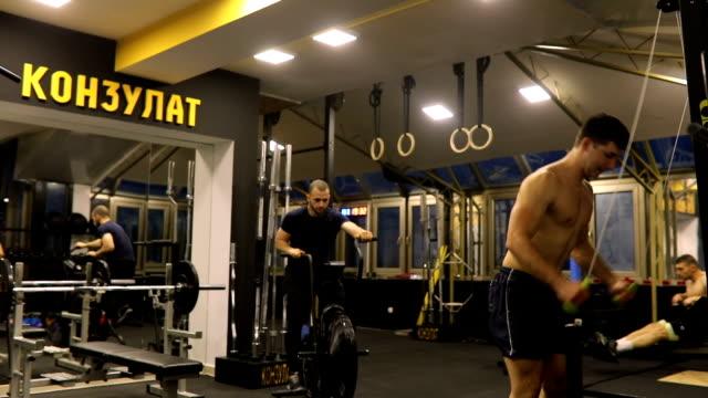 jungs üben zusammen im fitness-studio - heimtrainer stock-videos und b-roll-filmmaterial