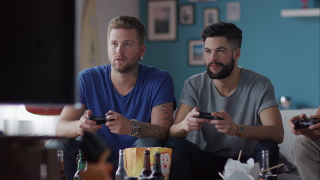 Guys sitting on couch playing video games and cheering