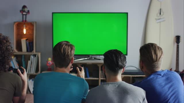 guys sitting on couch playing video games - computer game control bildbanksvideor och videomaterial från bakom kulisserna