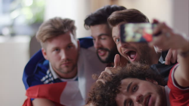 guys sitting on couch taking selfies - fan enthusiast stock videos & royalty-free footage