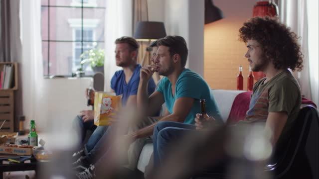 jungs sitzen auf couch-watching horror movie - ekel stock-videos und b-roll-filmmaterial