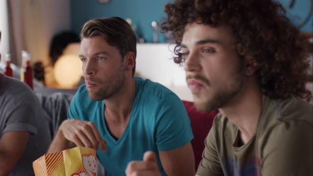 vídeos de stock, filmes e b-roll de caras sentada no sofá assistir tv - indústria televisiva