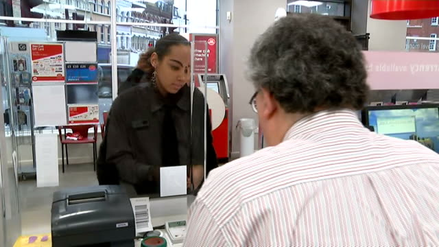gvs euros customer buying euros at counter / 'travel money' sign / customer buying euros at bureau de change in post office - kommode stock-videos und b-roll-filmmaterial