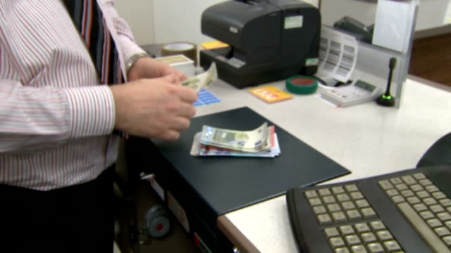 london int various of euros being counted onto surface by post office worker / customer at counter - post office stock videos & royalty-free footage