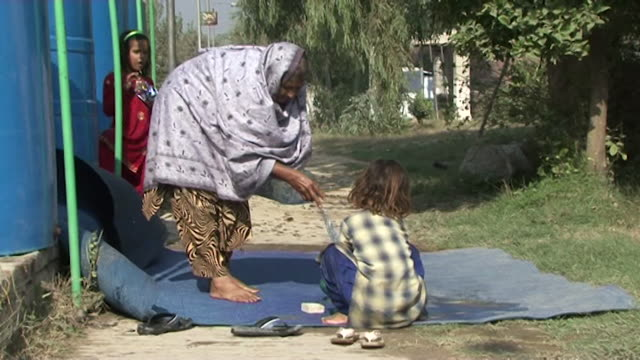 gvs from pakistan where people have been displaced following floods and attacks from the taliban are on the rise causing the gun market to expand - senior women stock videos & royalty-free footage