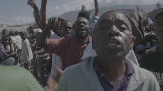 gvs from portauprince haiti where president michel martelly has resigned and thousands of opposition members still protest saying their candidates... - 対決点の映像素材/bロール