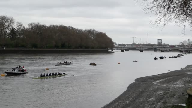 gvs from the river thames, surrey side, of the oxford team training, craven cottage and the river ahead of the boat race. - oxford england video stock e b–roll