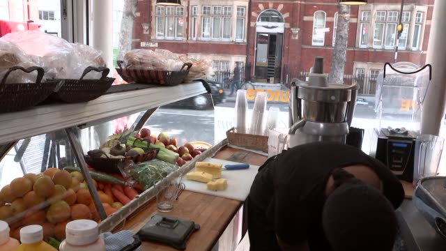 London GVs juice bar worker cutting pineapple / worker blending fruits for smoothie