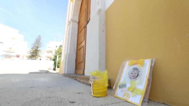 gvs of a tribute to madeleine mccann is left outside the church of nossa senhora da luz in praia da luz portugal close to where madeline mccann went... - madeleine mccann stock videos & royalty-free footage