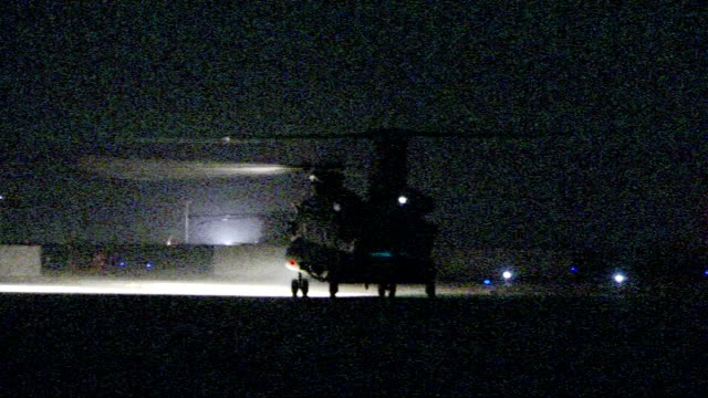 gvs of camp bastion airfield by night afghanistan helmand province camp bastion helicopter inside hangar as bv soldier and reporter walk up to it... - helicopter rotors stock videos and b-roll footage