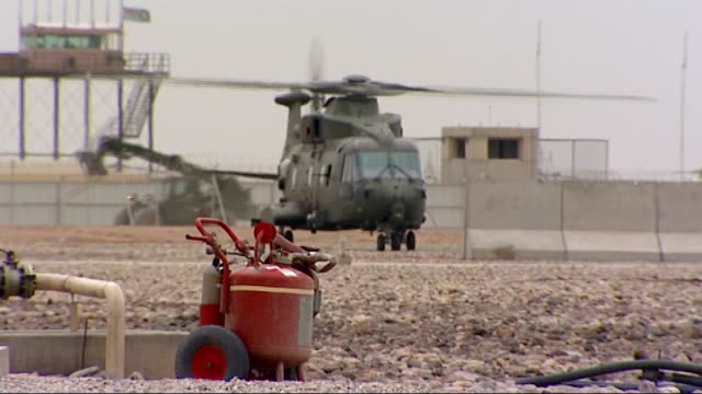gvs of helicopters at camp bastion gvs of chinook parked and crew members at work around it griffon and chinook helicopters parked at airfield pan... - アパッチヘリコプター点の映像素材/bロール