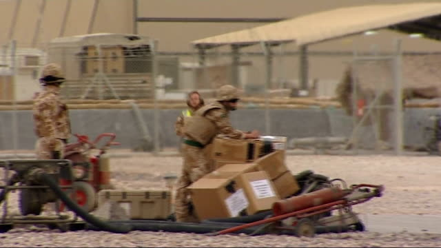 GVs of helicopters at Camp Bastion One soldier leaning on boxes of supplies Sea King helicopter parked with rotors turning Long shot of helicopter...