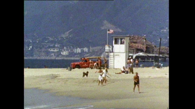 stockvideo's en b-roll-footage met gvs of people and lifeguards on venice beach; 1972 - venice california