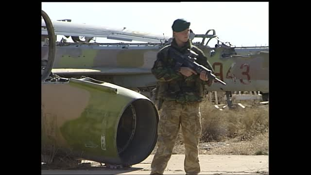 gvs of royal marines patrolling bagram airbase; afghanistan: bagram: bagram airbase: ext 00:19:21 gvs old wrecked planes on tarmac two armed american... - snowcapped mountain stock videos & royalty-free footage