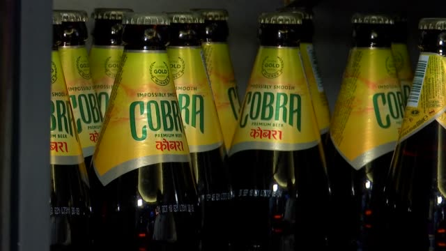 London Covent Garden INT GVs staff member unpacking Cobra beers and stacking them in fridge / cap taken off beer and beer poured into glass GVs The...