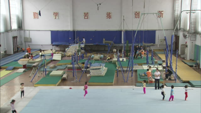 gym interior w/ young girls working out on floor mat below, boy practicing pommel circles, child on trampoline, others working out bg. olympic... - school child stock videos & royalty-free footage