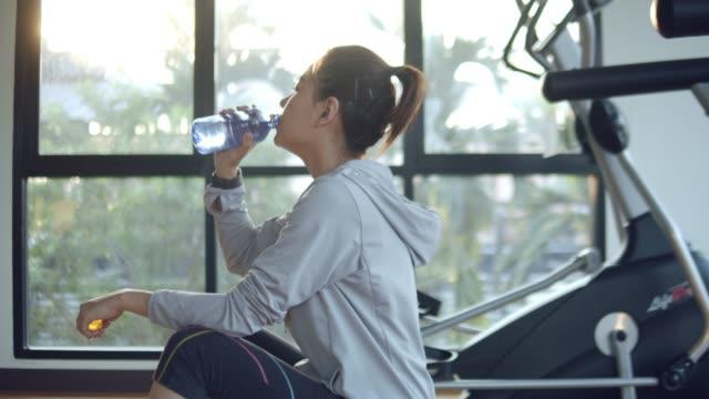 vídeos de stock, filmes e b-roll de mulher de ginásio bebendo - acabando