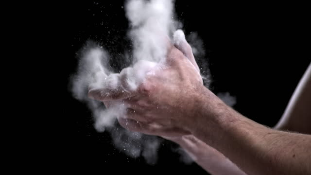SLO MO Gymnast clapping his chalky hands together