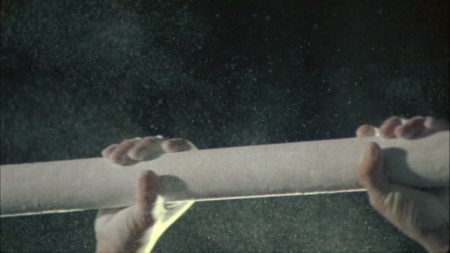 stockvideo's en b-roll-footage met ecu, slo mo, gymnast grabbing parallel bar in cloud of rosin - grijpen