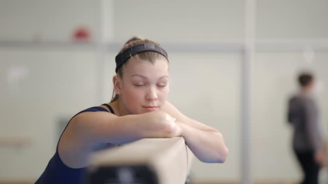 ms gymnast resting chin on balance beam / vancouver, british columbia, canada - nur weibliche teenager stock-videos und b-roll-filmmaterial