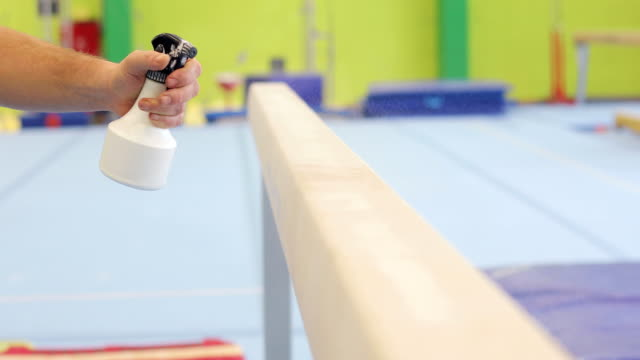 gymnastics athlete spraying horizontal bar for better grip - horizontal bar stock videos and b-roll footage
